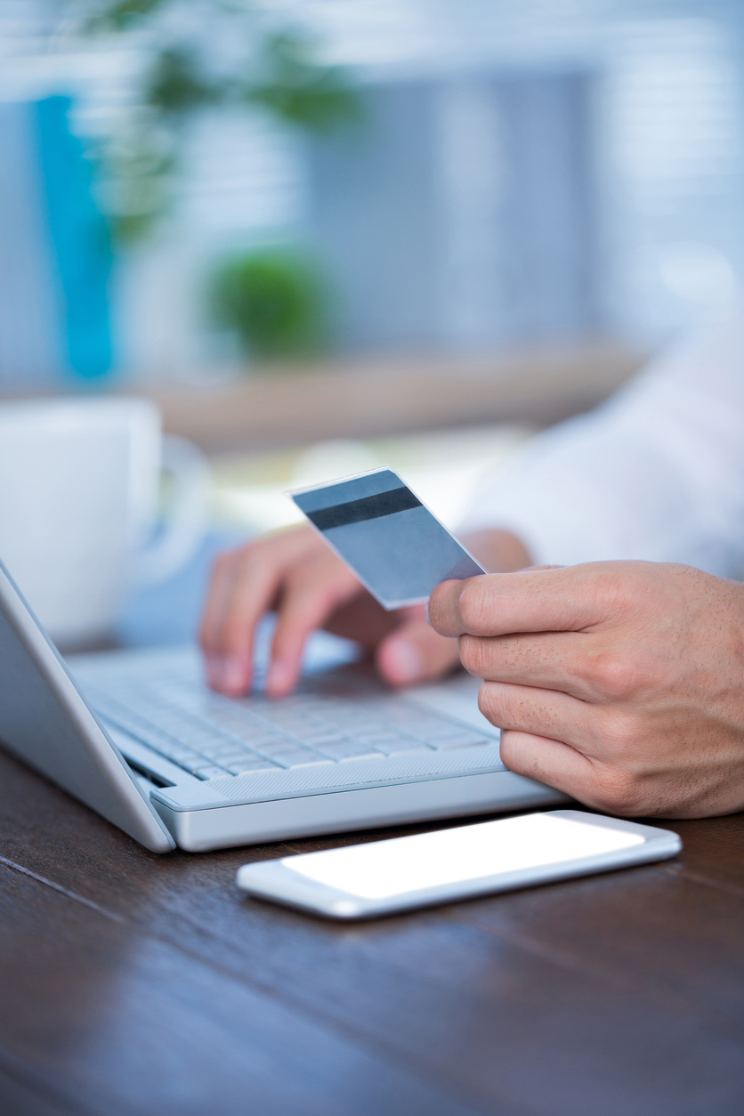 Close up view of a businessman using a credit card and typing